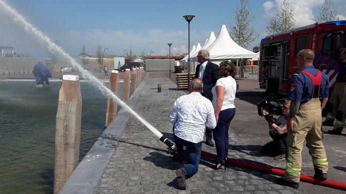 Ko Kallewaard (links), Adrie van der Maas (midden) en Janneke Janssen (rechts) spuiten de Oude Haven vol met water.