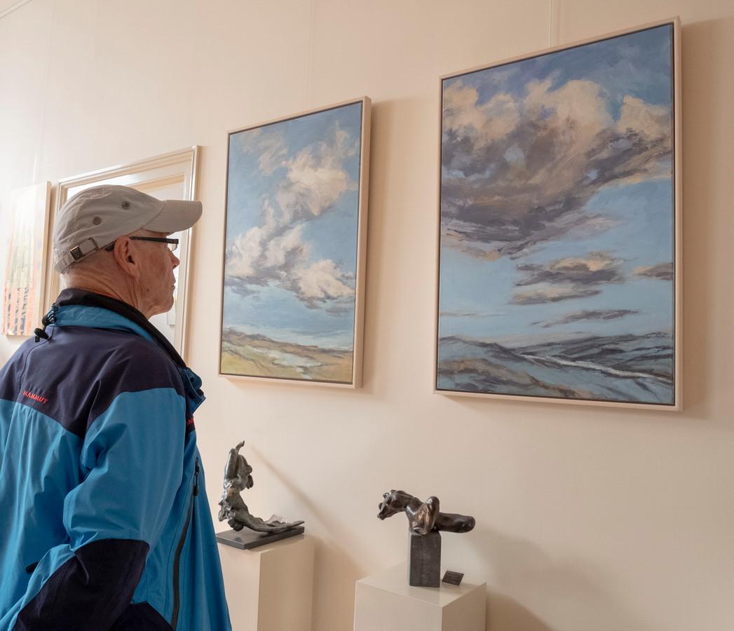 Een bezoeker bekijkt werken van Margriet de Vries in galerie Het Moment in Zierikzee.