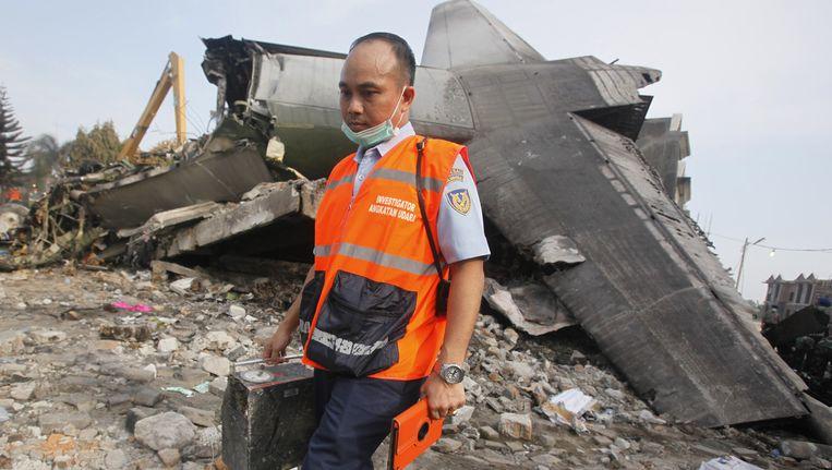 Een onderzoeker bij het wrakstuk van het neergestorte vliegtuig in Medan. Beeld ap