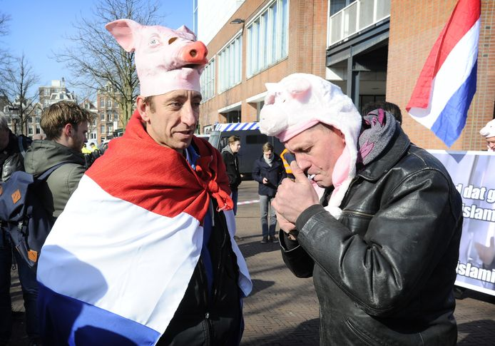 Twee demonstranten met de voor Pegida kenmerkende varkenskoppen