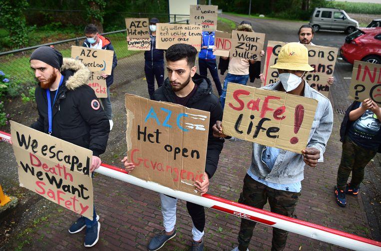 Voor de poort van het asielzoekerscentrum in Zweeloo protesteren asielzoekers tegen de ongelijke behandeling van asielaanvragen. Beeld Marcel van den Bergh