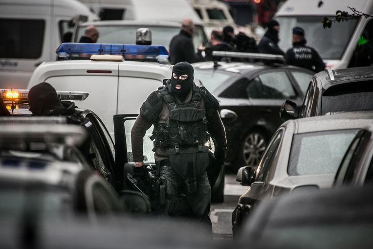 Een agent maakt zich op voor een huiszoeking en arrestaties in Molenbeek. Beeld Bas Bogaerts