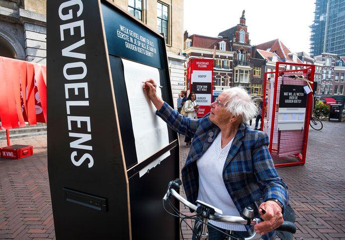 Annemarie Roebert (86) uit Utrecht schrijft haar mening over de Gouden Koets op een groot vel papier.