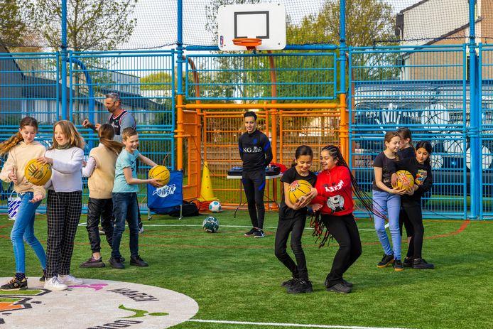 Basketballer Henk Pieterse en balgoochelaar Nasser El Jackson tijdens een workshop ter gelegenheid van de heropening van de Blauwe Voetbalkooi bij de Zesde Haren in Den Bosch. FC Den Bosch Foundation en Jeugdfonds Sport en Cultuur 's-Hertogenbosch-Vught willen ieder kind laten sporten.