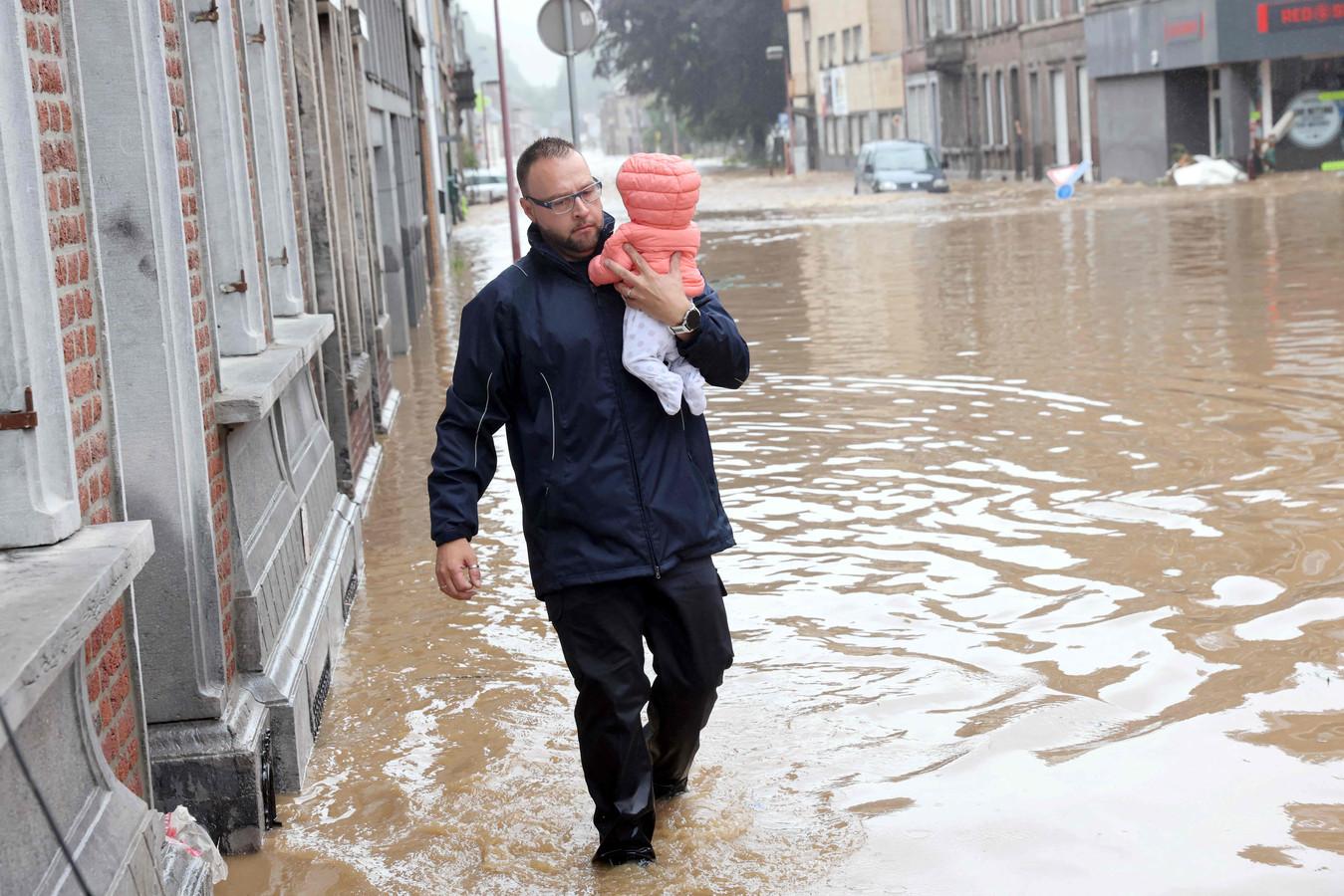Een vader brengt zijn baby in veiligheid in het ondergelopen Hognoul (Awans, provincie Luik).