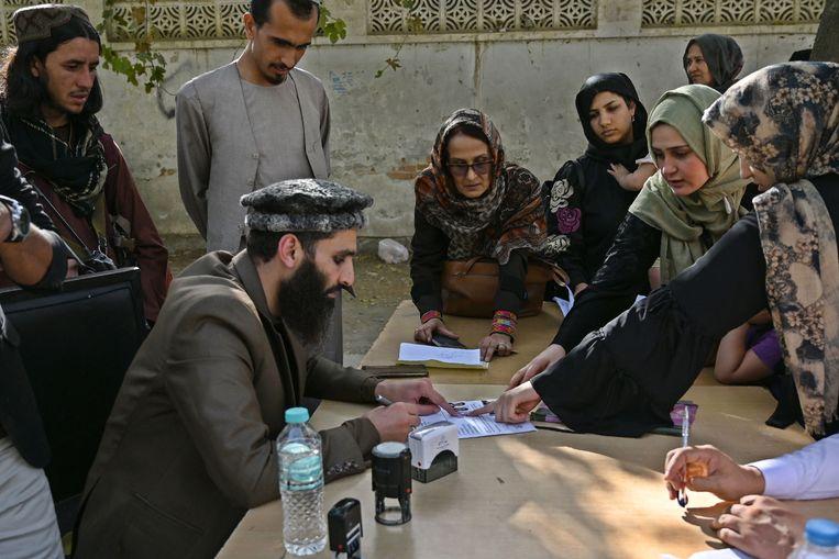 Documenten van mensen die een paspoort aanvragen worden gecontroleerd in Kabul. Beeld AFP