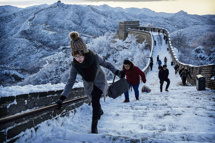 Chinese toeristen houden zich goed vast terwijl ze over de Chinese Muur lopen. Het internationale toerisme groeit zo snel, dat het afkopen van de CO2-uitstoot van pakketreizen geen oplossing voor het broeikaseffect is.  Bron: Getty Images