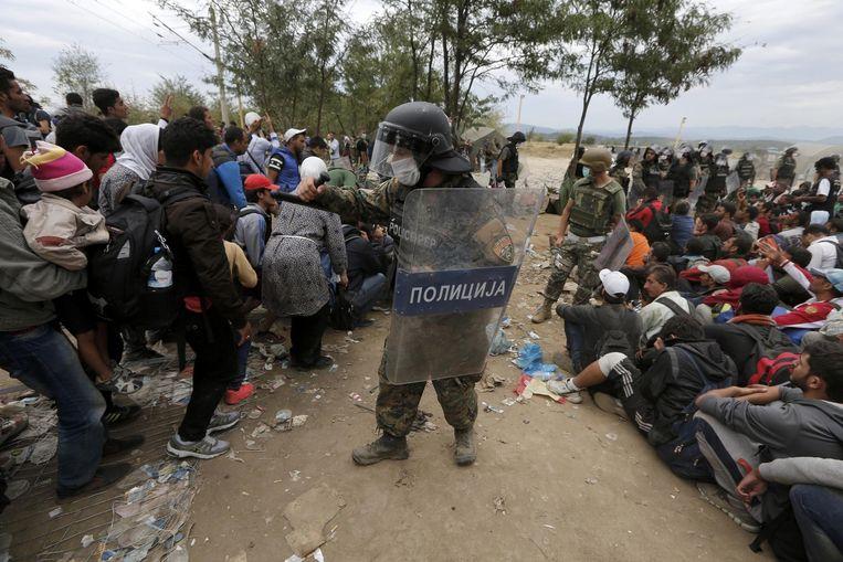 Macedonische politieagenten houden vluchtelingen tegen die de grens met Griekenland willen oversteken. Beeld reuters
