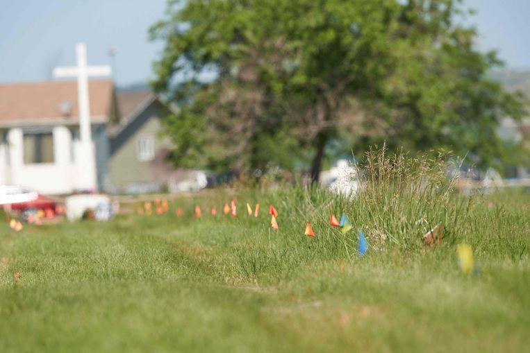 Vlaggetjes geven de plek aan waar de stoffelijke overschotten van 751 kinderen zijn begraven bij de voormalige Marieval kostschool.  Beeld AFP