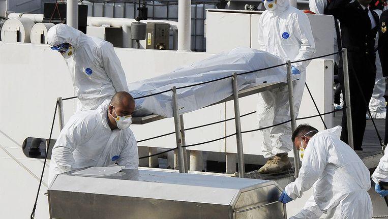 Reddingswerkers brengen de lichamen van overleden migranten op de Middellandse Zee weg Beeld AP
