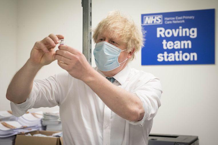 Premier Boris Johnson bekijkt een dosis van het Oxford/AstraZeneca Covid 19 vaccin. Beeld AFP