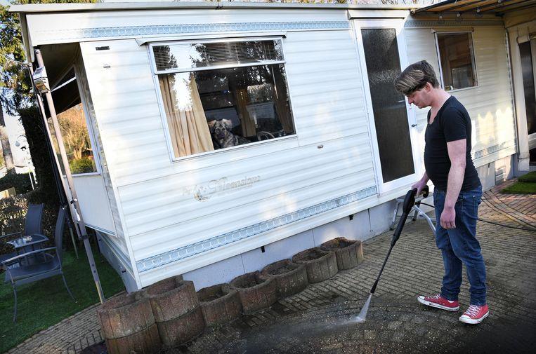 Noud Manders bij zijn stacaravan, waar hij van maart tot november in woont. Beeld Marcel van den Bergh / de Volkskrant