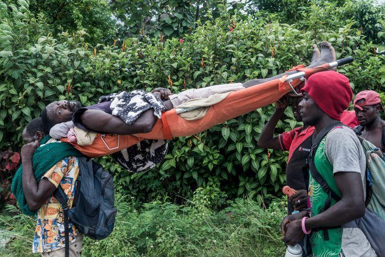 Omdat het rampgebied vaak moeilijk toegankelijk is moeten gewonden vaak naar klinieken worden gedragen.  Beeld AFP