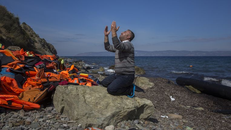 Een vluchteling valt neer om te bidden nadat hij en verschillende anderen het Griekse eiland Lesbos veilig wisten te bereiken.