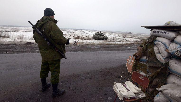 Een pro-Russische rebel staat op wacht bij een checkpoint. Beeld AFP