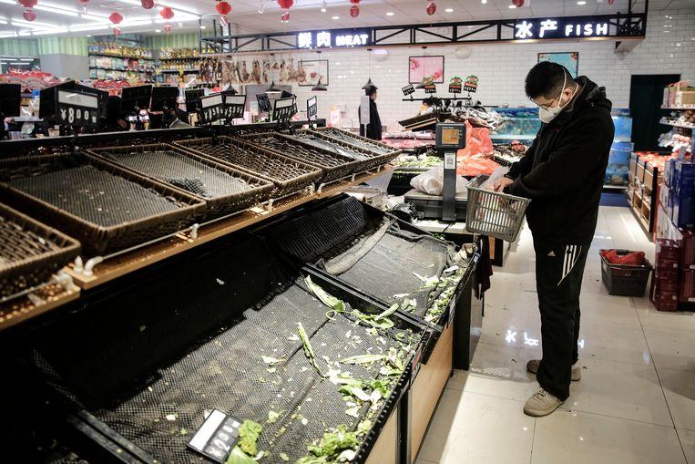 Groenten kopen met een mondmasker op de markt van Wuhan. Beeld Getty Images