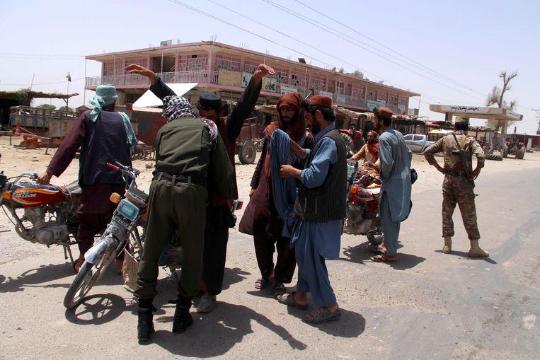 Beveiligers controleren mensen en voertuigen aan een controlepunt in de Afghaanse provincie Helmand. Beeld EPA