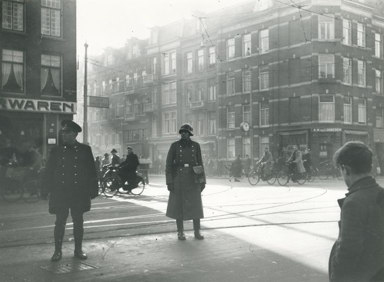 Amsterdam, 1941. Een Duitse soldaat regelt met een Nederlandse politieman het verkeer op de kruising van de Ceintuurbaan en Van Woustraat. De Duitsers moeten wennen aan het in hun ogen chaotische fietsverkeer. Beeld J.J. Meun/Niod, Beeldbank WO2