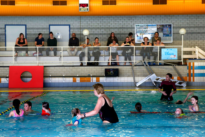 Ouders in het Caribabad in Gorinchem kijken toe bij de zwemles van hun kind.