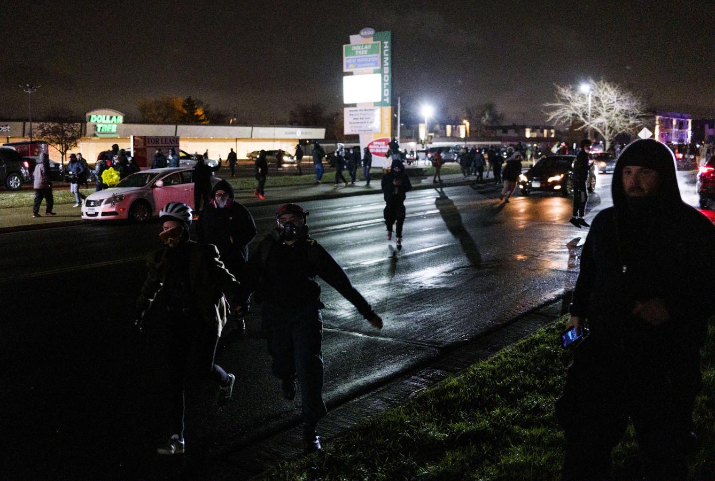Des personnes fuient les agents des forces de l'ordre près du quartier général de la police de Brooklyn Center le 13 avril 2021 à Brooklyn Center, Minnesota.