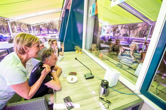 Carla en Gerrit Breukelman en hun dochter konden als een van de eersten bij zorgcentrum 't Welgelegen hun (schoon)moeder/oma in levende lijve zien en een praatje met haar maken. Er zat alleen wel een raam tussen.