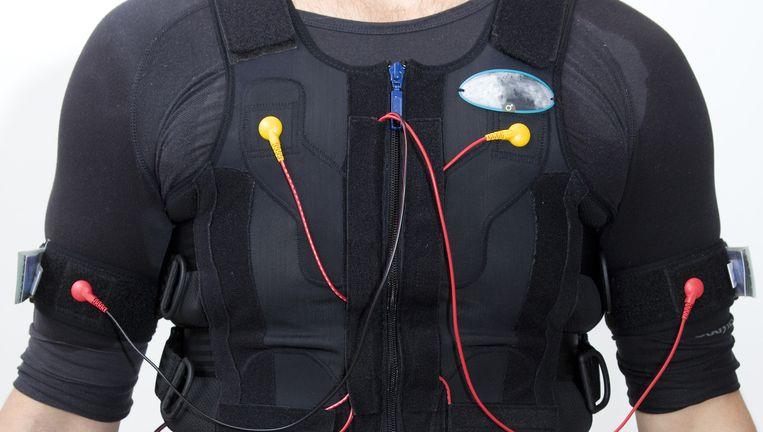 Een medewerker van Bodytec Lounge demonstreert het sportkorset met elektroden, die de spieren stimuleren. Beeld Io Cooman