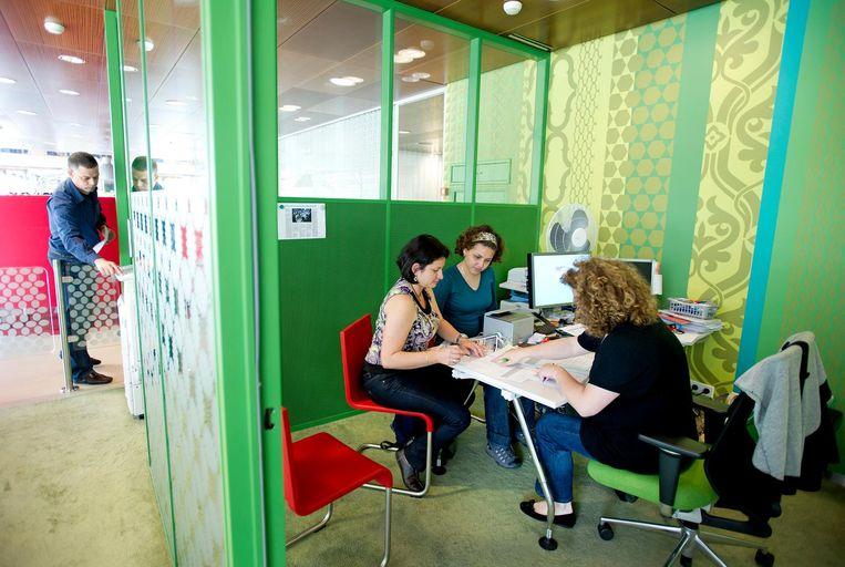 Twee Colombiaanse kennismigranten in het expatcentrum in het WTC in Amsterdam. Beeld Olaf Kraak