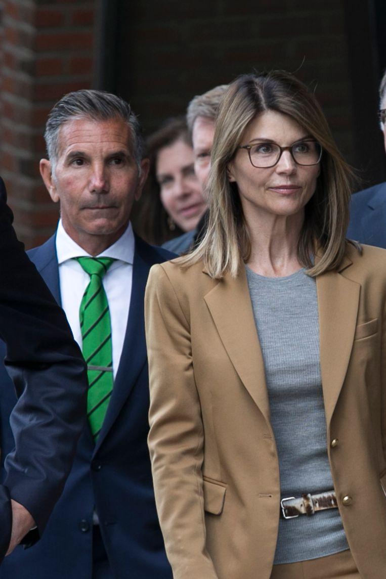 Actrice Lori Loughlin (r) en haar man Mossimo Giannulli verlaten de rechtbank in Boston. Beeld EPA