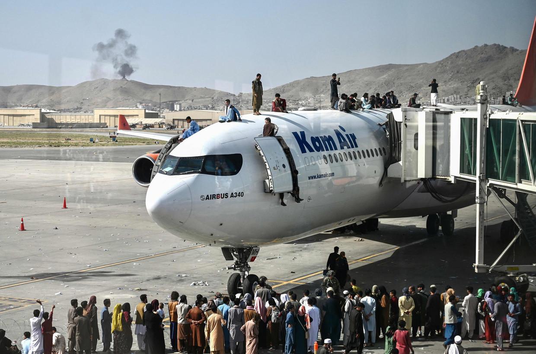 Wanhopige burgers bestormen het tarmac van de luchthaven van Kaboel en klimmen op vliegtuigen in een poging te ontsnappen, waarna ze kansloos te pletter storten. Beeld AFP