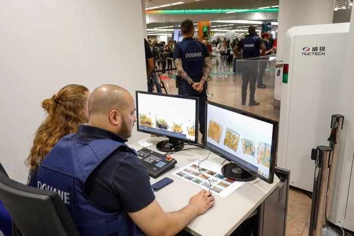 Douanepersoneel in Brussel controleert de bagage. Marcel (niet op de foto) zorgt dat deze mensen met de nieuwste apparatuur kunnen werken om snel analyses te doen.