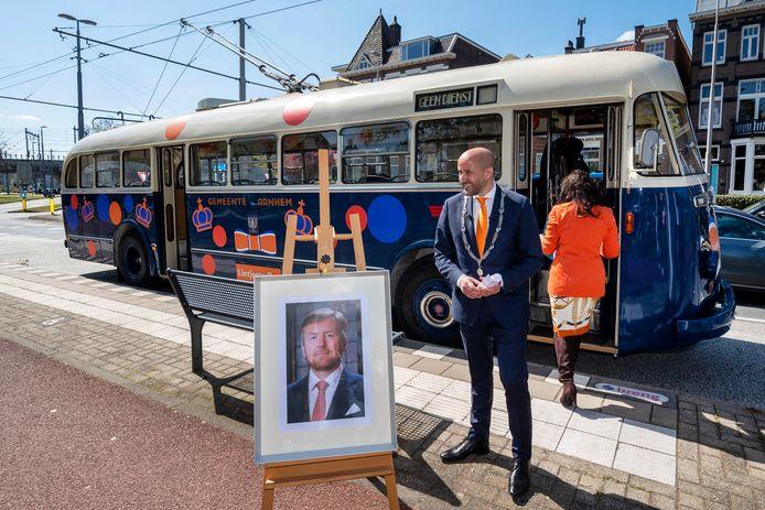 Burgemeester Ahmed Marcouch rijdt met een oude trolleybus en een portret van de koning door de stad om Arnhemmers een  Koninklijke Onderscheiding uit te reiken.