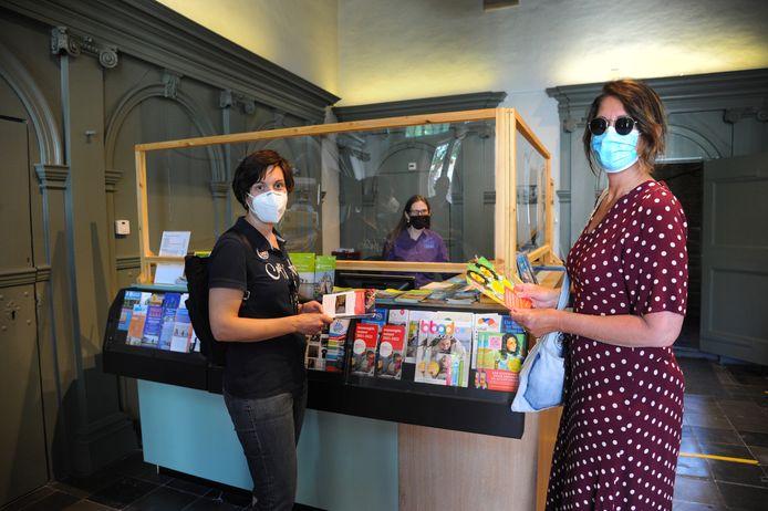 Rondom de balie van het Veers Museum ligt toeristische informatie. Astrid en Anita Scholer-Kortink (l) komen de eerste dag van hun bezoek aan Veere direct kijken wat er te doen is in de regio. Marianne Riemens (midden) helpt hen.