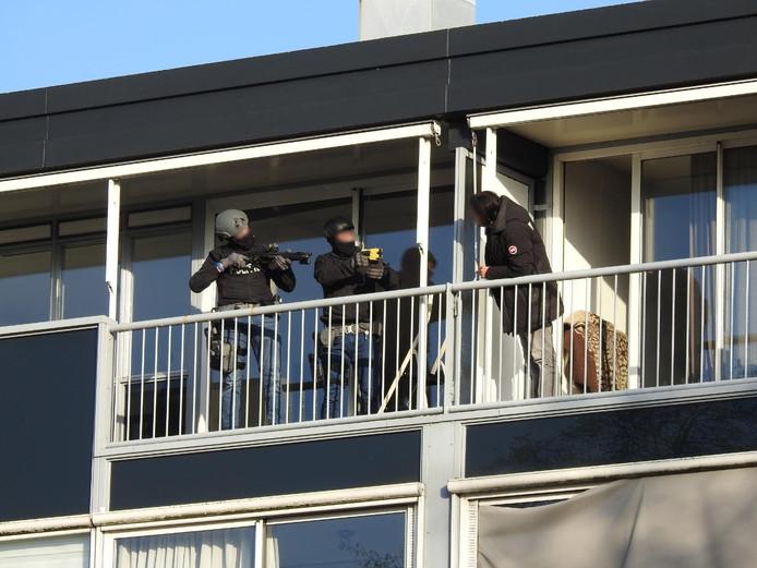 Leden van het arrestatieteam op het balkon van de woning aan de Poldermolen dreef in Gouda.