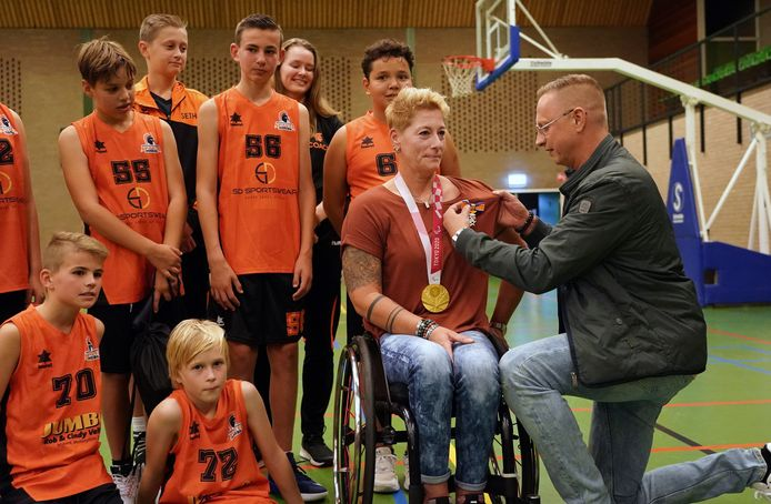 Gouden paralympische sporter Chèr Korver ontvangt koninklijke onderscheiding van haar broer Maurice, te midden van het basketbalteam van haar neefje waar ze coach van is.