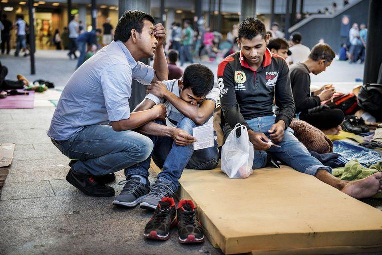 Migranten in het Keleti-treinstation in Boedapest. Beeld Eric De Mildt