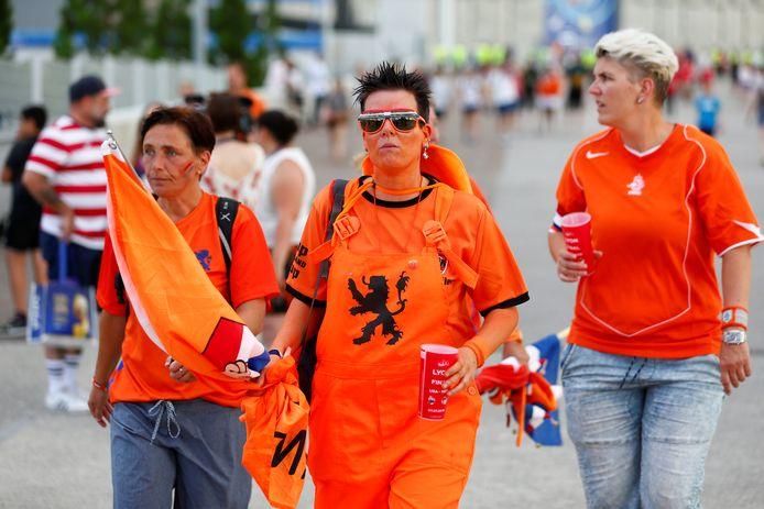 Teleurgestelde Nederlandse fans druipen af na de verloren finale.