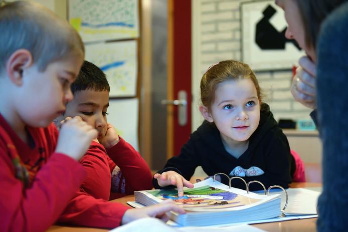 V.l.n.r. Lucas, Ibrahim en Mia krijgen op de Gummarusschool in Steenbergen extra taalles van juf Esther van Deurse.