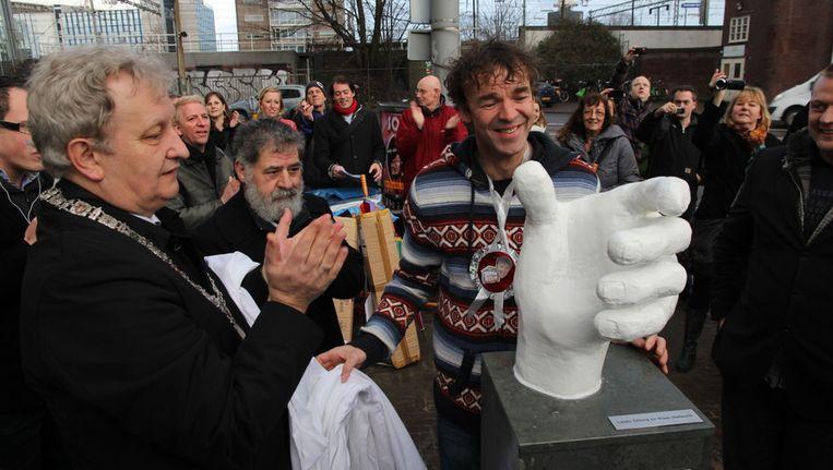 Burgemeester van der Laan (l) bij de onthulling van het beeld, in het midden, achter het beeld, de Aardigste Amsterdammer Herman Kuijl. © redactie Beeld