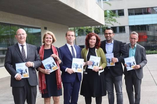 De nieuwe wethouders van Eindhoven met in hun hand het nieuwe coalitieakkoord. V.l.n.r. Marcel Oosterveer (VVD), Monique List (VVD), Stijn Steenbakkers (CDA), Renate Richters (GroenLinks), Yasin Torunoglu (PvdA) en Jan van der Meer (GroenLinks).