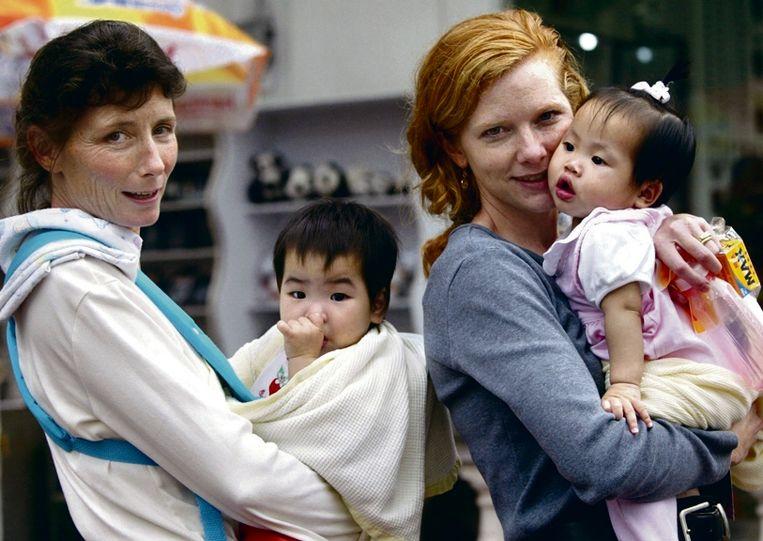 April 2003: Amerikaanse vrouwen wandelen door een park met hun net geadopteerde Chinese baby's in Guangzhou.  Beeld REUTERS