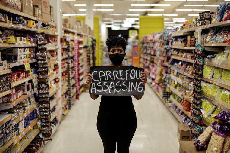 Een vrouw in een Carrefour-filiaal in Rio de Janeiro met een spandoek waarop de tekst 'Carrefour moordenaar' geschreven staat. Beeld EPA