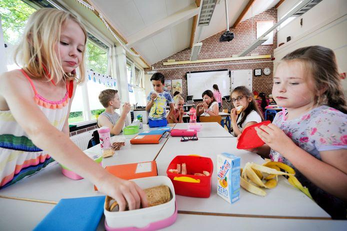 Scholieren houden een gezonde lunchpauze op de basisschool.