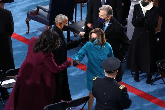 Barack Obama en Michelle Obama begroeten Nancy Pelosi, voorzitter van het Huis van Afgevaardigden, en haar man Paul Pelosi met een vuistje.