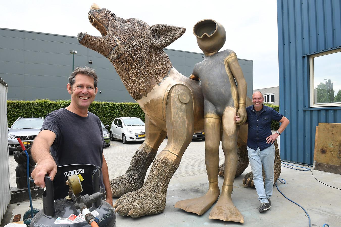 Albert Dedden (links) en Paul Keizer van kunstenaarsduo Space Cowboys bij de Waterwolf en de Aquanaut, op het terrein van  bronsgieterij Kemner in Cuijk. Daar leggen ze de laatste hand aan het beeld, dat op de Waalkade in Nijmegen wordt geplaatst.