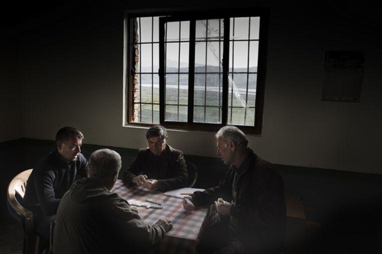 Mannen uit het dorp spelen domino. Uit het raam is de Vjosa te zien. Beeld Daniel Rosenthal