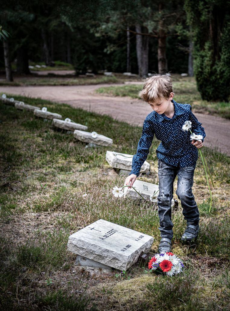 Kinderen leggen bloemen op graven van het ereveld in Loenen. Beeld Koen Verheijden