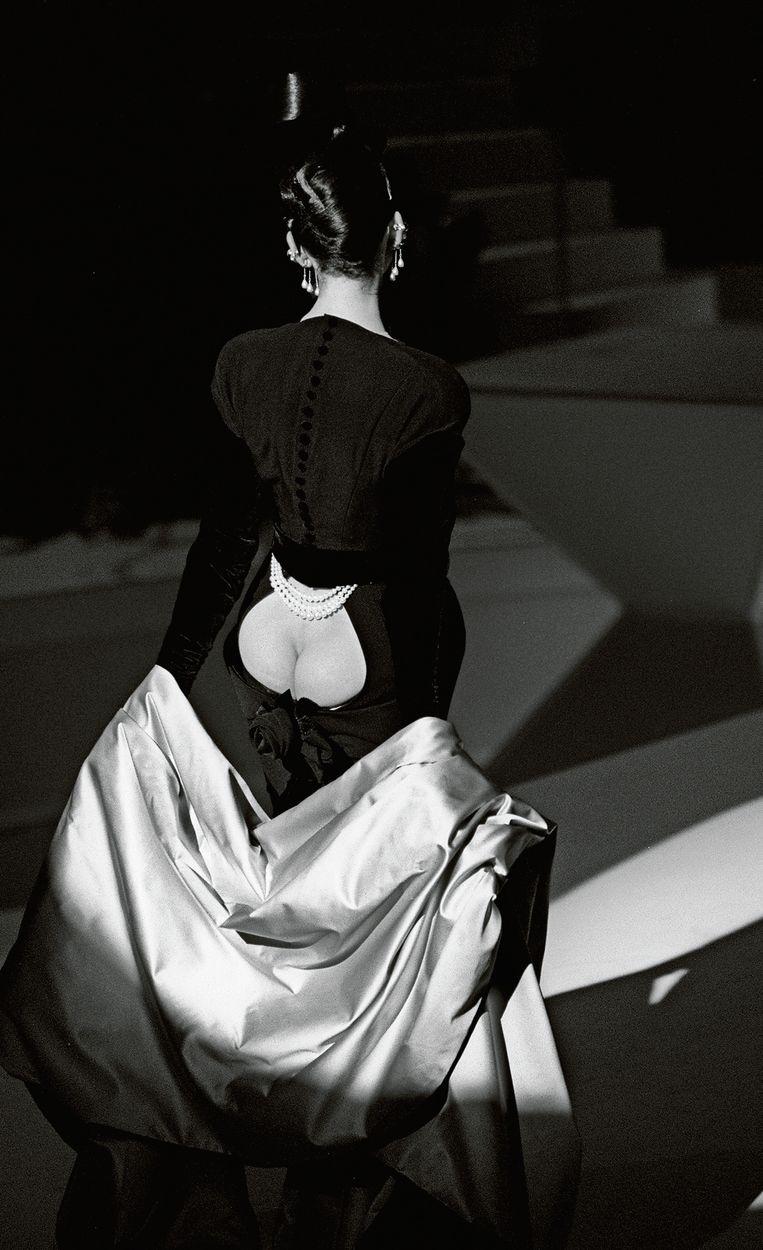 Een model laat een zijden cape zakken om het zogeheten bildecolleté te tonen op de catwalk in 1995.  Beeld rv