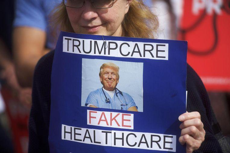 Een demonstrant houdt een bordje omhoog tegen 'Trumpcare'. Beeld null