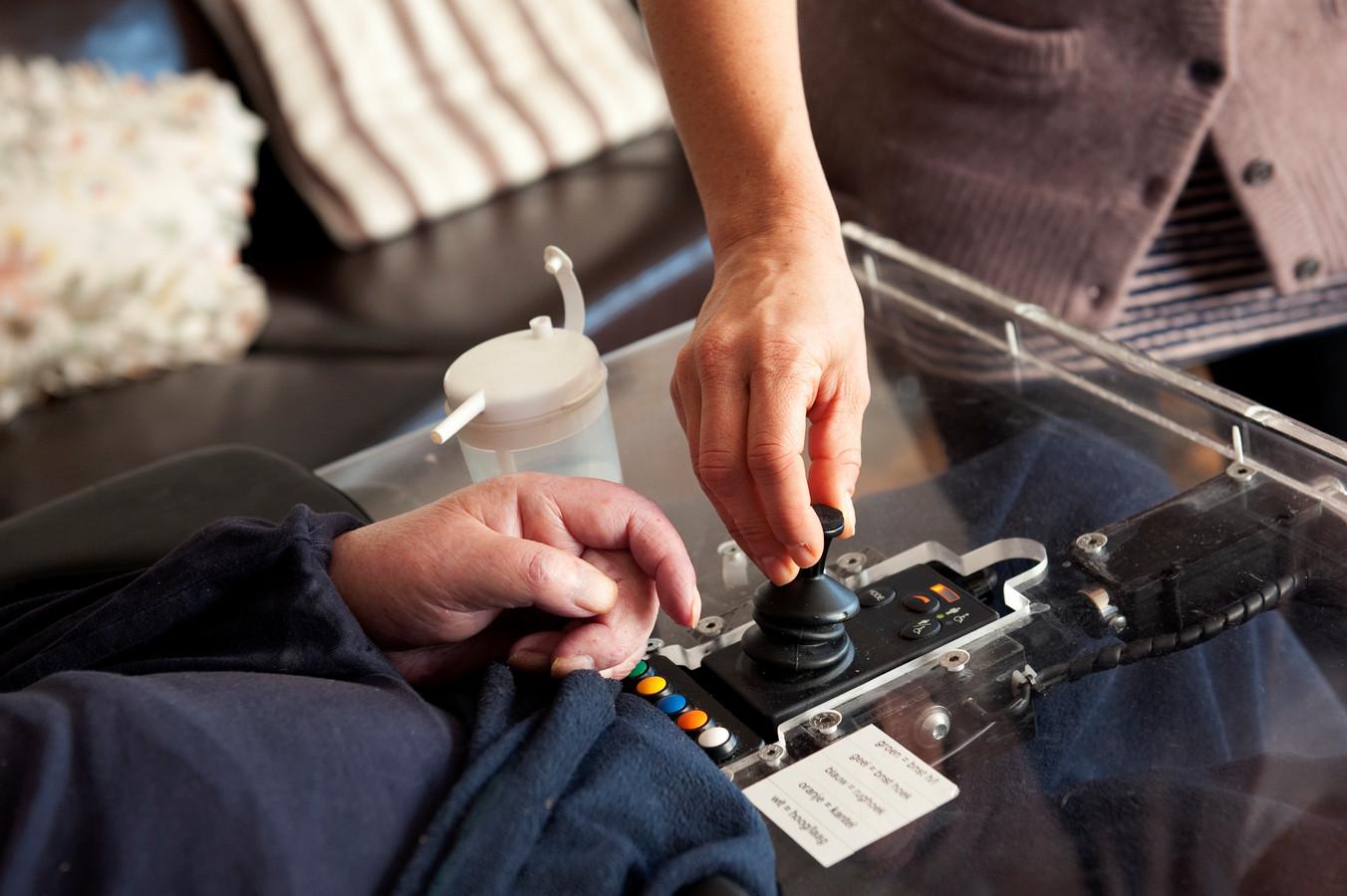 Thuiszorg-medewerkster bedient een elektrische rolstoel van een cliënt.