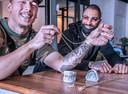 Guus en Denzel, op tafel (en over Guus zijn tanden) de grills die hij zelf maakt.